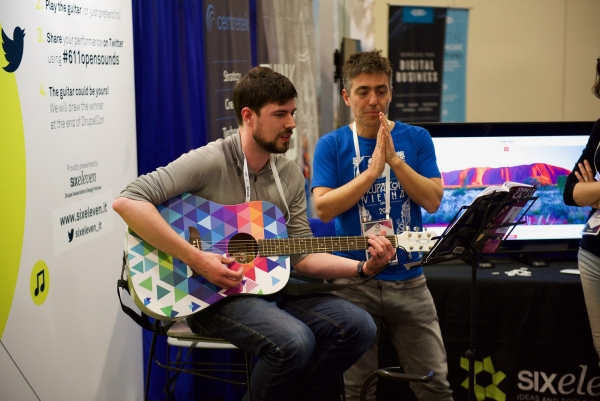 Ryan Bateman playing the guitar in the expo hall at DrupalCon Nashville