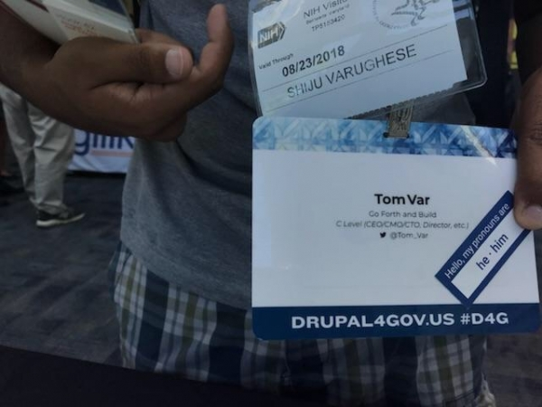 An attendee at DrupalGovCon displaying personal pronoun sticker on their badge